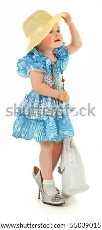 Fashion-monger. Girl in blue dress with a bag and a hat