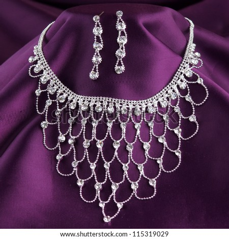 fashion necklace and earrings on purple silk background