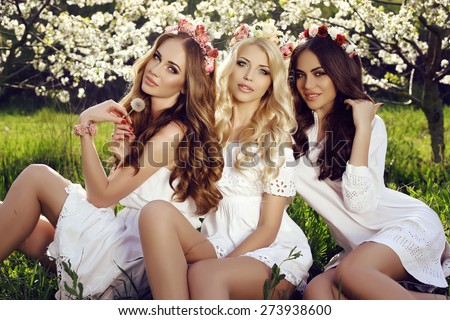 fashion outdoor photo of beautiful charming women in elegant dresses with headband on hair posing in spring blossom garden