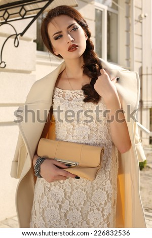 fashion outdoor photo of beautiful elegant girl with dark hair and bright makeup wearing white wool coat and lace dress,posing on the street