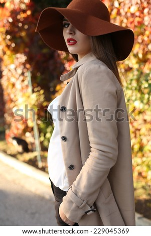 fashion outdoor photo of beautiful elegant ladylike woman with dark hair wearing coat and felt hat,posing in autumn park