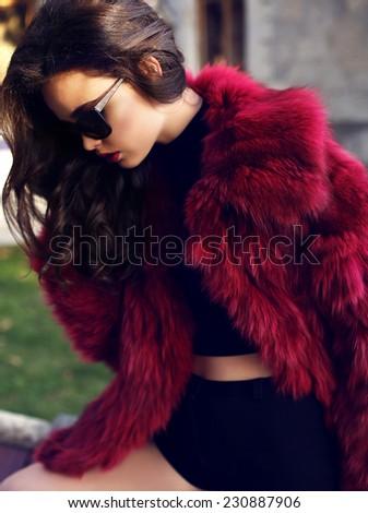 fashion outdoor photo of beautiful elegant woman with dark hair wearing elegant fur coat and sunglasses