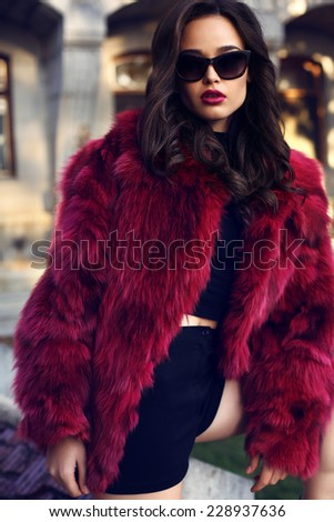 fashion outdoor photo of beautiful elegant woman with dark hair wearing luxurious red fur coat and sunglasses,posing in autumn park
