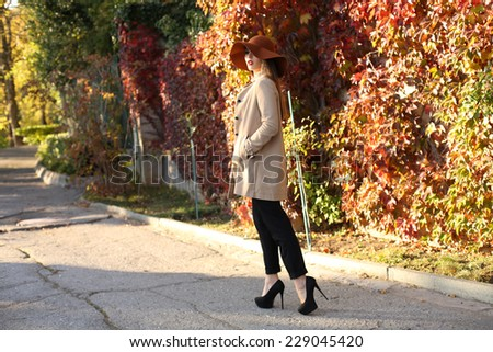 fashion outdoor photo of beautiful elegant woman with dark straight hair wearing elegant coat and hat,posing in autumn park