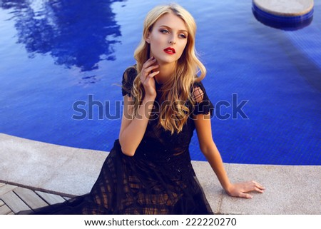 fashion outdoor photo of beautiful girl with blond curly hair in elegant lace dress posing beside a swimming pool