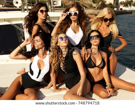 fashion outdoor photo of beautiful girls in elegant swimsuit relaxing on yacht in the sea #748794718