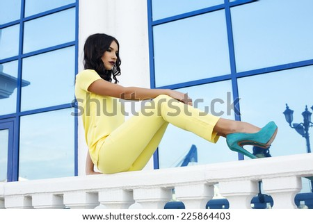 fashion outdoor photo of beautiful glamour woman with dark hair wearing elegant yellow suit and blue shoes