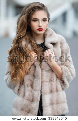 fashion outdoor photo of beautiful lady with dark hair wearing elegant coat,leather gloves and felt hat,posing in autumn park. Beautiful fashionable woman standing on the city street.