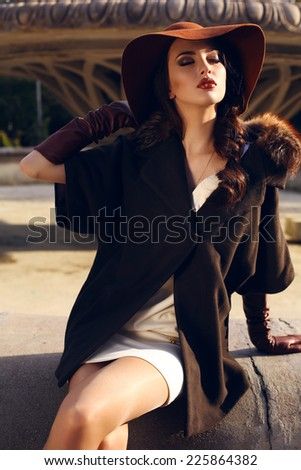 fashion outdoor photo of beautiful lady with dark hair wearing elegant coat with fur, felt hat and leather gloves,sitting beside a fountain