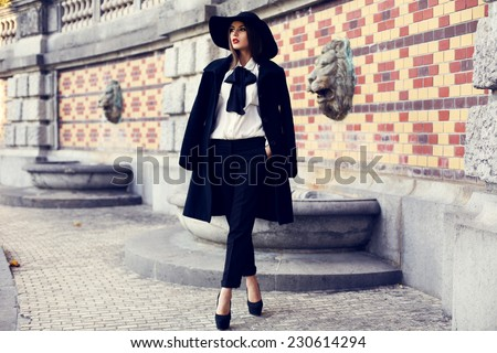 fashion outdoor photo of beautiful ladylike woman with dark hair wearing elegant coat and felt hat and posing in autumn park