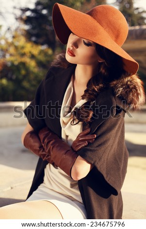 fashion outdoor photo of beautiful ladylike woman with dark hair wearing elegant coat with fur,felt hat  and leather gloves