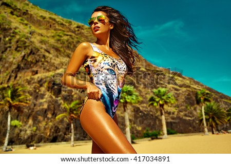 fashion outdoor photo of beautiful sexy hot woman model with dark hair in  colorful bikini relaxing on summer beach behind blue sky and palms