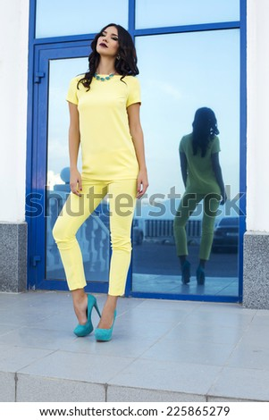 fashion outdoor photo of beautiful sexy woman with black hair in elegant yellow suit and blue shoes posing beside a big window