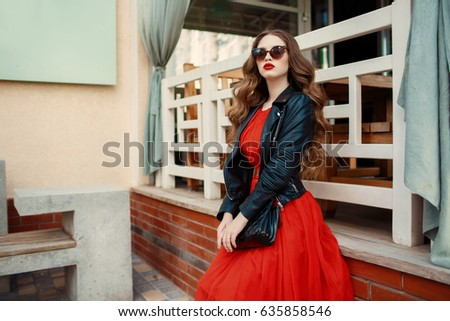 Fashion outdoor photo of gorgeous long hair woman in elegant red dress and black leather jacket. Fashionable hipster girl in trendy clothes posing at city street lifestyle portrait. #635858546
