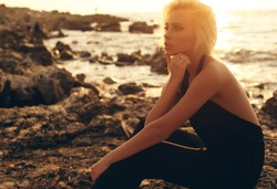 fashion outdoor photo of gorgeous sensual girl with blond hair in elegant clothes posing at sunset beach