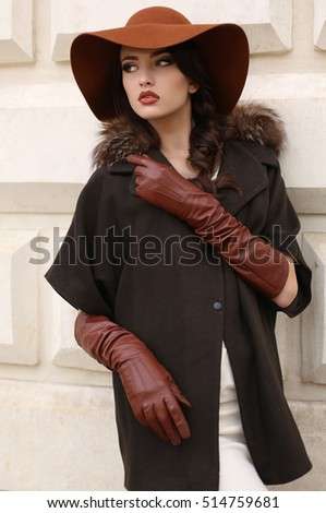 fashion outdoor photo of gorgeous sensual woman with dark hair in elegant luxurious coat, wool hat and leather gloves, walking by autumn city