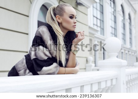 fashion outdoor photo of sexy beautiful woman with long straight hair wearing luxurious fur coat