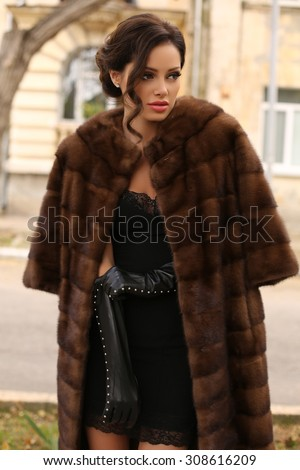 fashion outdoor photo of sexy glamour woman with dark hair wearing luxurious fur coat and leather gloves,posing  in autumn park