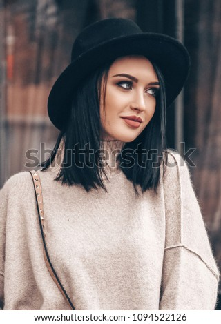 fashion outdoor photo of young pretty woman with short dark hair in elegant outfit and black hat walking on the street #1094522126