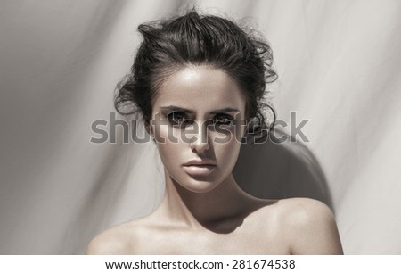Fashion outdoor portrait of a sexy brunette girl with stylish hairstyle. Smoky eyes.