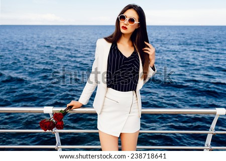 Fashion outdoor portrait of sexy beautiful woman with brunette hairs, wearing stylish white suit  and sunglasses, holding bouquet of red roses after date, amazing view on deep blue sea.