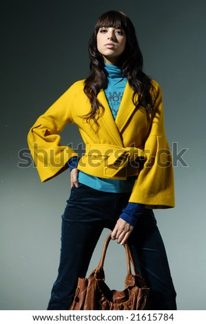 Fashion photo, model with a bag posing on light background
