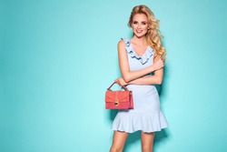 Fashion photo of a beautiful elegant young blonde woman in a pretty blue dress holding handbag posing over blue background. Fashion spring summer photo