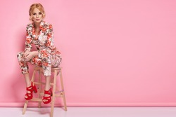 Fashion photo of a beautiful elegant young woman in a pretty suit with flowers holding handbag posing over pink background. Fashion photo