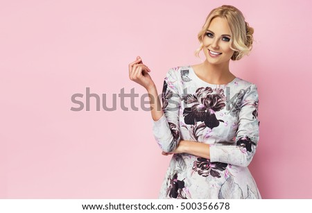 Fashion photo of a beautiful young woman in a pretty dress with flowers posing over pink background. Fashion photo