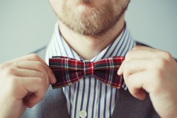 Fashion photo of a man with beard correcting his bowtie
