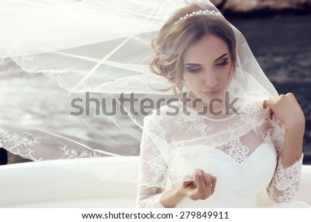 fashion photo of beautiful sensual bride with dark hair in luxurious lace wedding dress posing on yacht