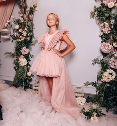 fashion photo of beautiful small girl with blond hair in elegant dress posing in decorated studio with flower's arch