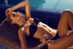 fashion photo of beautiful tanned woman with blond hair in elegant black bikini relaxing beside a swimming pool