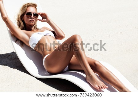 Stock Photo fashion photo of beautiful tanned woman with blond hair in elegant white bikini relaxing on white chair.