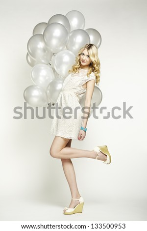 Fashion photo of beautiful woman with balloons. Girl posing. Studio photo
