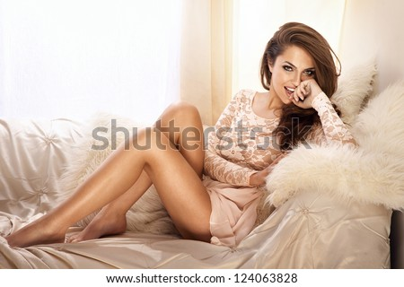 Fashion photo of beautiful young woman wearing lace dress, relaxing and smiling in bright room, on the white couch. - stock photo