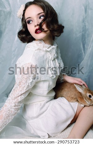 Fashion photo of beautiful young woman with curly hair wearing a retro style in white lace dress, pointe shoes, holing a rabbit and posing at studio