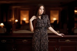 Fashion photo of beautiful young woman with long dark hair in elegant black dress posing over dark background. Fashionable and self-confident girl.
