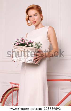 fashion photo of elegant and sexy red woman in white dress, red shoes with beautiful hairstyle posing at studio with classic interior near the bicycle and holding a box with wildflowers
