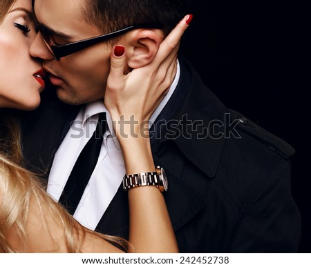 Fashion photo of office romance of sexy lovers,pretty blond woman with watch,red lipstick,and handsome brunette businessman wearing in suit,tie,glasses,they are hugging and kissing on Valentine\'s day