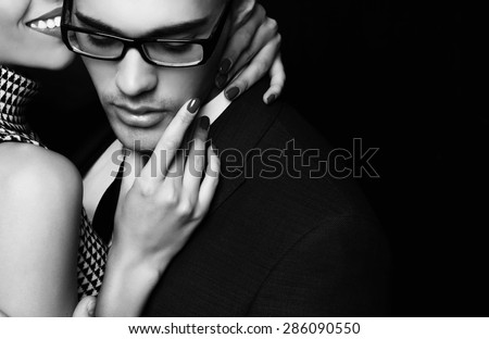 Fashion photo of office romance of sexy young lovers of beautiful blond woman and handsome brunette businessman wearing in format suit,tie,glasses, they are hugging and kissing on Valentine\'s day