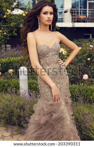 fashion photo of sensual glamour woman with long curly hair in luxurious beige dress walking in summer garden
