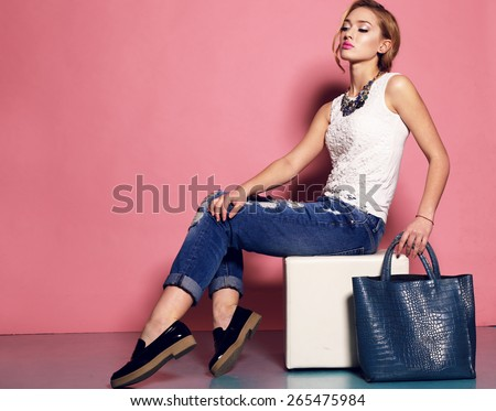 Fashion photo of sexy beautiful woman with blond curly hairstyle wearing a  blue jeans,white top,black shoes and jewelry holding a bag and posing on a chair #265475984