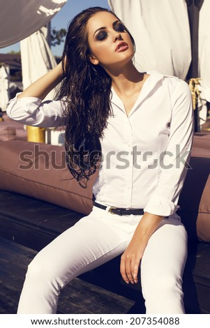 fashion photo of sexy glamour woman with long dark wet hair in white shirt and pants sitting on beach