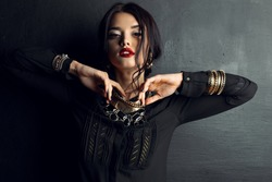 Fashion photo of sexy Indian woman with dark hair and bright make-up wearing black shirt and  luxurious gold necklace,bracelets, earrings posing at studio