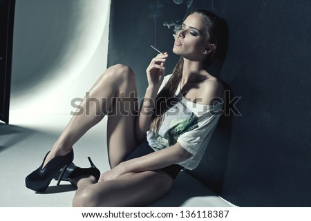 Fashion photo of sexy woman smoking a cigarette