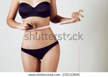 Fashion photo of sexy young woman in lingerie with slim body sitting on a diet and measuring the waist with a centimeter tape