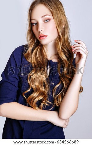 Fashion photo of young curly blonde girl on white background in studio. Dressed in a blue shirt and jeans. #634566689