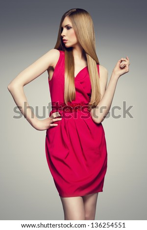 Fashion photo of young magnificent woman in red dress.