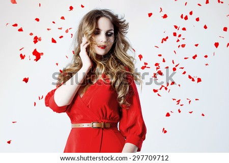 Fashion photo of young magnificent woman in red dress amid rose petals